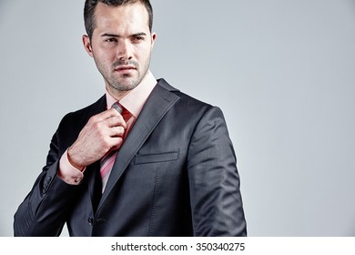 Businessman arranging his dress isolated over grey