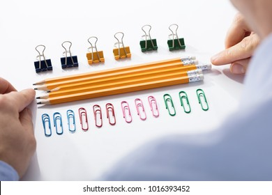 Businessman Arranging The Pencils In Between The Row Of Colorful Pins And Paper Clips