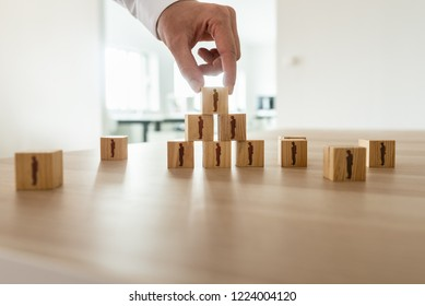 Businessman arranging wooden cubes with people silhouette in a pyramid shape with others scattered on office desk. Conceptual of business organization, human resources and teamwork.