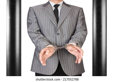 businessman arrested with handcuffs in jail isolated on white background with clipping path
