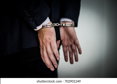 Businessman arrested with handcuffs on back for corruption and stealing millions of dollar euro money bank fraud and bribery. hands wide open