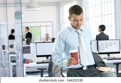 Businessman arriving to office holding coffee to go.