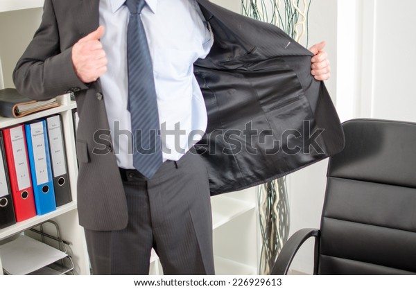 Businessman arriving at office and taking off his jacket
