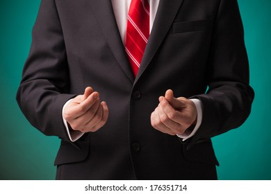 Businessman asking for money in black suit and red tie on green background.