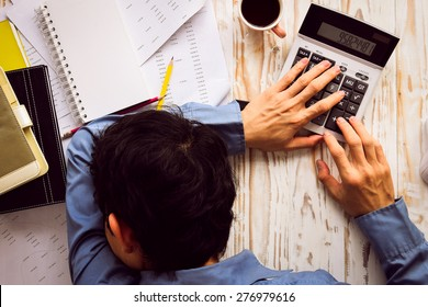 Businessman asleep at office desk with finance sheet calculator and coffee.(concept for overworked)