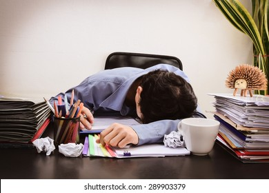 Businessman asleep at office desk with finance sheet calculator and coffee.(concept for overworked) (Dark vintage tone)