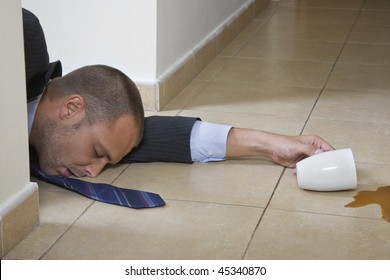 Businessman asleep in the office with spilt coffee