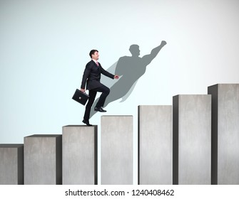 Businessman with aspiration seeks forward and up on the career ladder with superhero shadow on the wall.