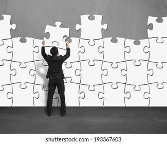 Businessman assembling puzzles wall