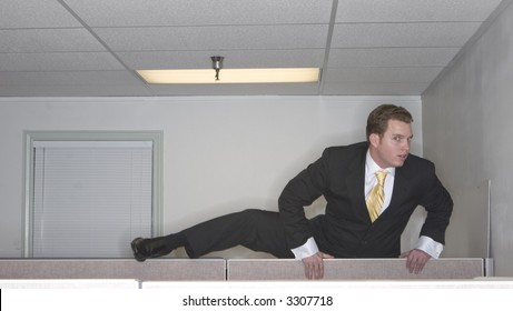 Businessman attempts to climb up over his cubicle in an attempt to get out of his office while looking at the camera