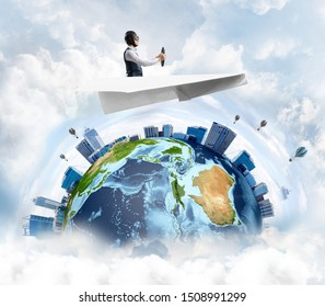 Businessman in aviator hat sitting in paper plane and holding steering wheel. Pilot driving paper plane in cloudy blue sky. Spherical view of modern city with high skyscrapers and sea line.