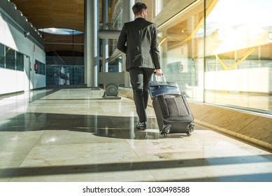 businessman back and legs walking with luggage at the airport