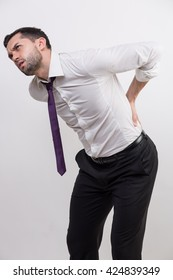 Businessman with back pain holds his back in a studio