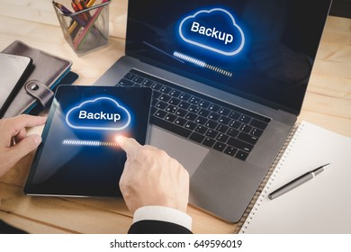 Businessman backup data from laptop and tablet device to cloud service