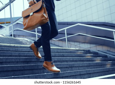 Businessman with bag in his hand walking down steps. Cropped shot of elegant man in suit taking step down on stairs.