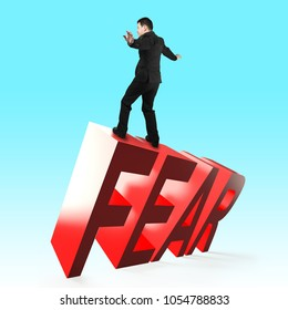 Businessman balancing on 3D red FEAR word falling. Concept of courage, overcoming fear and adversity.