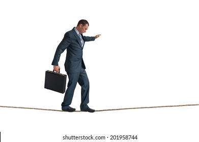 businessman balancing on a tightrope isolated on white