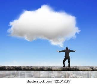 Businessman balancing on tightrope with white cloud, on blue sky cityscape background.