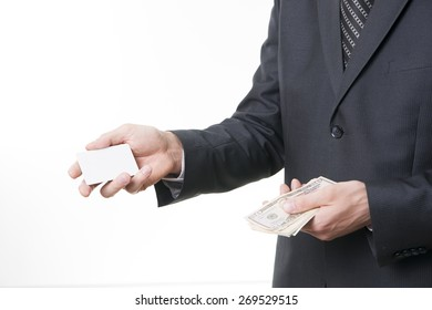 Businessman with bank card and dollars in suit on white background.