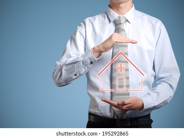 Businessman or banker man holding home or house in hands