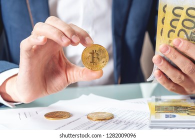 Businessman banker sitting at the table with papers holding a coin bitcoin. The concept of exchange and sale of cryptocurrency for Euro