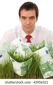 Businessman with banknotes in grass - green business concept, isolated, focus on foreground