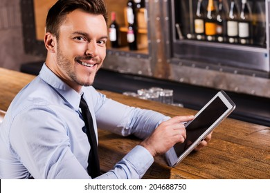 Businessman in bar. Handsome young man in shirt and tie working on digital tablet and smiling while sitting at the bar counter