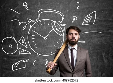 Businessman with bat and with clock sketch on blackboard in the background