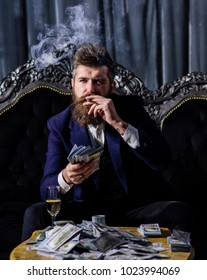 Businessman with beard has cigar, champagne and dollars. Success, business, wealth concept. Bearded man with confident face in classic interior. Millionaire in elegant suit smokes on luxurious sofa.