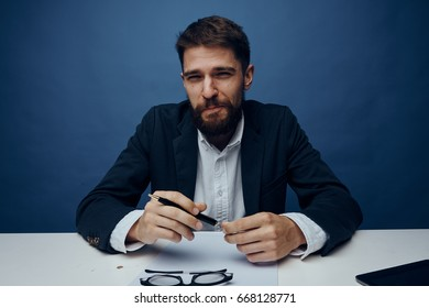 Businessman with a beard at his desk holds a pen, emotions, office, work, papers, documents.