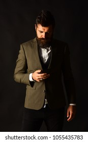 Businessman with beard holds mobile phone. Man in smart suit types message or browses internet on brown background. Man with serious face uses gadget. Business and technology concept