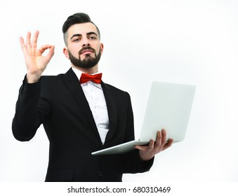 Businessman with beard or manager with confident face holds laptop in hand and shows ok sign, isolated on white background, copy space. Concept of IT business