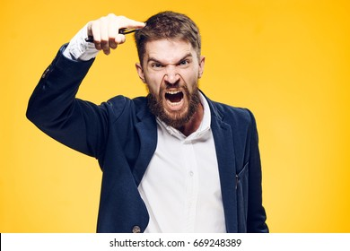 Businessman with a beard on a yellow background, emotions, portrait, boss, anger, scream, aggression.