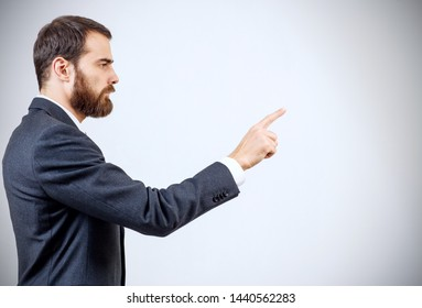 Businessman with beard pointing to something or touching by forefinger. Side view. Over gray background.