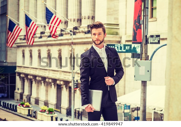 Businessman with beard working in New York, wearing black suit, white shirt, holding laptop computer, standing on Wall Street outside office building with American flags. Instagram filtered effect.