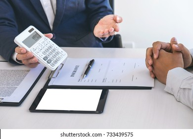 Businessman being analysis and making the decision a car insurance policy, Agent man is using calculator to presentation detail and waiting for his reply to finish.