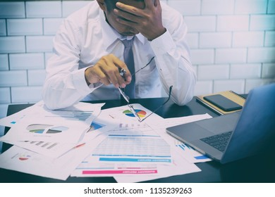 Businessman being depressed by working in office. Strain, business man to think and not Work with stress Pretending to put his hand to the head.