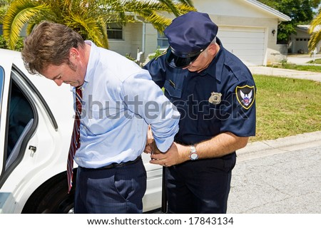 Businessman being handcuffed and placed under arrest in front of his home.