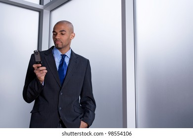 Businessman beside an office window, dialing a number on his cell phone.