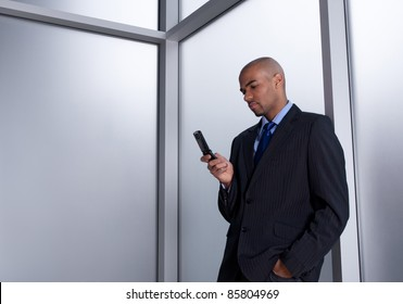 Businessman beside an office window, sending a message with his cell phone.