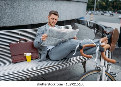 Businessman with bike reading newspaper on bench
