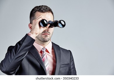 Businessman with binocular isolated over grey
