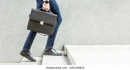 Businessman with black briefcase in hand walking up on stairs. business goal, improvement, progress, Increase and growth concept. Outdoor closeup shot. in grey wall copy space.