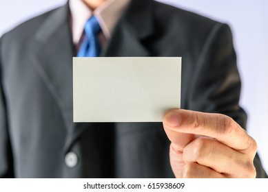 Businessman in a black business suit / formal attire, he presents / shows a blank white business card. Business cards typically include name, company or business affiliation and contact information.