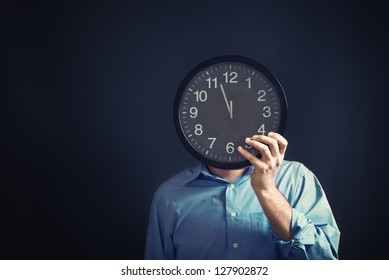 Businessman with black clock in front of his head, deadline concept. Not enough time to finish the job. Time management.
