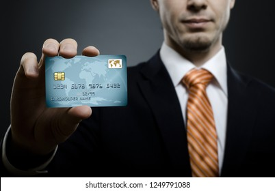 businessman in black costume and orange necktie reach out on camera and show credit card, close up