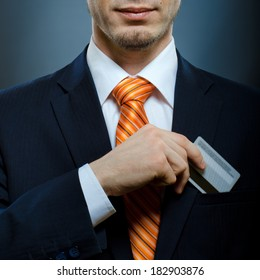businessman in black costume and orange necktie put or take out credit card in pocket