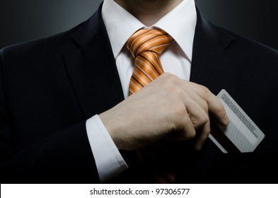 businessman in black costume and orange necktie put or take out credit card in pocket, close up