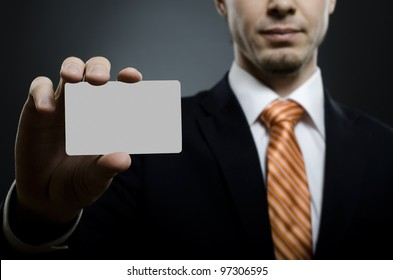 businessman in black costume and orange necktie reach out on camera and show credit card or visiting card, close up