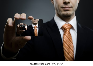 businessman in black costume and orange necktie reach out on camera and show credit card , close up